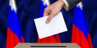 Election in Russia. The hand of man putting his vote in the ballot box. Russian flags on background. - Светлый Путь